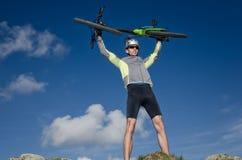 Ciclyst soulevant le vélo de montagne au-dessus du sien chef heureux avec le succ Images libres de droits