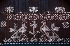 在木屋墙壁上的被绘的装饰在Cicmany,斯洛伐克 免版税图库摄影
