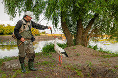 Cicogna e pescatore fotografia stock