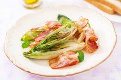 Cicoria al forno con bacon, cipolle Immagini Stock