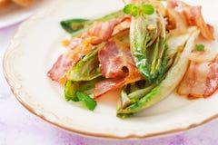 Cicoria al forno con bacon, cipolle Immagine Stock