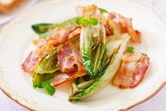Cicoria al forno con bacon, cipolle Fotografie Stock