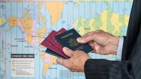 Cidadão do Reino Unido ou dos E.U. com passaportes e mapa do mundo dos fusos horários Fotos de Stock