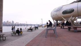Cidadãos de Seoul que sentam-se no banco, leitura, fala, relaxando fora vídeos de arquivo