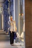 Cidade da noite da compra do indicador da mulher nova Foto de Stock