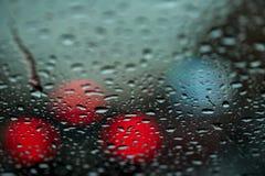 Cidade da noite na chuva, na vida urbana e nas luzes de rua, tráfego denso Gotas da água no vidro Fundo abstrato de urbano Imagens de Stock Royalty Free
