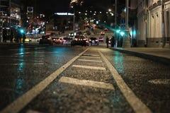 Cidade da noite O asfalto no foco é visível seu equipamento técnico Asfalto após a chuva molhada Fotos de Stock Royalty Free