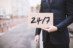 Cidade da rua, um homem que guarda um sinal dentro suas mãos com a inscrição foto de stock