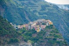 A cidade de Corniglia, uma das cinco cidades pequenas no parque nacional de Cinque Terre, Itália Vista do navio da excursão foto de stock royalty free