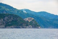 A cidade de Corniglia, uma das cinco cidades pequenas no parque nacional de Cinque Terre, Itália Vista do navio da excursão fotos de stock