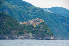 A cidade de Corniglia, uma das cinco cidades pequenas no parque nacional de Cinque Terre, Itália Vista do navio da excursão imagens de stock
