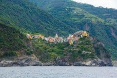 A cidade de Corniglia, uma das cinco cidades pequenas no parque nacional de Cinque Terre, Itália Vista do navio da excursão imagem de stock royalty free