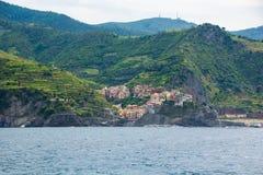 A cidade de Manarola, uma das cinco cidades pequenas no parque nacional de Cinque Terre, Itália Vista do navio da excursão imagens de stock royalty free