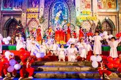 CIDADE de NAMDINH, VIETNAME - 24 de dezembro de 2014 - crentes cristãos que cantam uma música de natal do Natal na Noite de Natal Foto de Stock