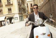 Cidade de Riding Scooter Through do homem de negócios imagem de stock royalty free