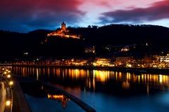 Cidade e castelo iluminados perto do rio Foto de Stock Royalty Free