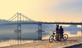 Cidade e ciclistas da noite perto da ponte fotografia de stock