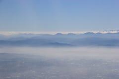 Cidade e montanha azul na névoa Fotos de Stock Royalty Free