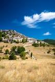 Cidade entre a grama amarela e o céu azul Fotografia de Stock