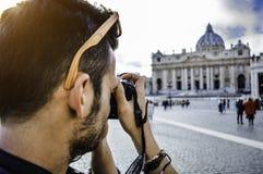 Cidade Estado do Vaticano, Roma, Itália Homem novo que toma a foto do quadrado de St Peter com a basílica famosa no fundo imagem de stock