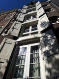 Cidade histórica com os obturadores de madeira da janela abertos Obturadores nas janelas de uma cidade europeia, Amsterdão fotografia de stock