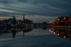 Cidade holandesa com a torre de igreja perto do Gouda com reflexões na água na hora azul fotografia de stock royalty free