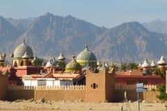 Cidade incomum árabe da pedra vermelha no fundo de montanhas bonitas no deserto fotos de stock royalty free