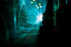 Cidade na noite na névoa densa Poluição atmosférica grossa em uma rua escura Silhuetas do homem na estrada Decoração da tabela Fo fotos de stock royalty free