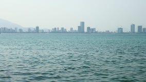 Cidade no horizonte com ondinhas do mar na parte dianteira de vídeos de arquivo
