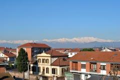 Cidade pequena na província italiana contra a montanha coberto de neve Imagem de Stock