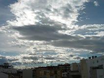 Cidade sob um sol escondido e uma viagem branca das nuvens foto de stock