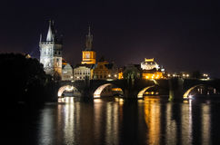 Cidade velha de Charles Bridge da capital Praga de República Checa na reflexão da noite de luzes no rio Fotografia de Stock