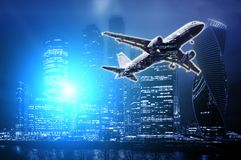 Cidades modernas dos arranha-céus do escritório das exposições dobro na noite com avião para decolar fotografia de stock