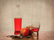 Cider and Apples. Still life of a bottle of cider with apples and a half filled glass on a textured background Royalty Free Stock Image
