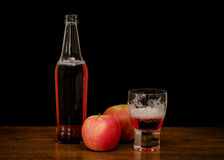Cider. Still life of a bottle of cider with glass and apples Royalty Free Stock Image