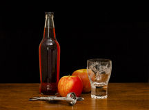 Cider. Still life of a bottle of cider with glass and apples Stock Photos