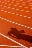 Cień mężczyzna na czerwonym bieg śladzie pojęcie odizolowywający sporta biel Obrazy Stock
