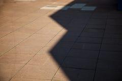 Cień od budynków tworzy abstrakcjonistycznych kształty na brukowych cegiełkach z pustą przestrzenią dla kopii Obrazy Royalty Free