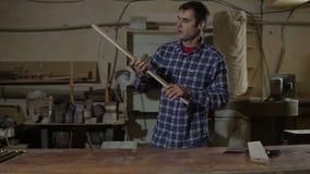 Cieśla poleruje drewnianą deskę z szklakiem na desktop Praca w ciesielka warsztacie zbiory