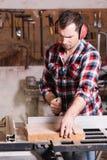 Cieśla pracuje na elektrycznym brzęczeniu zobaczył ciąć niektóre deski Zdjęcie Royalty Free