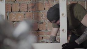 Cieśla stawia kleidło na drewnianej ramie dla lustra w czarnych rękawiczkach z tatuażami na rękach i nakrętce Pracownik zbiory wideo