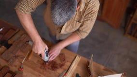 Cieśla używa świder obrotowy narzędzie o rzeźbi drewnianą deskę zbiory