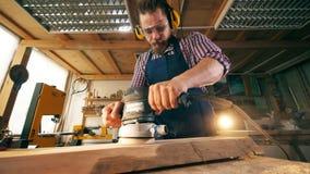 Cieśla używa polerowniczą maszynę przetwarzać drewno zdjęcie wideo