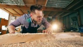 Cieśla usuwa drewnianych golenia od jego stołu Cieśla, rzemieślnika działanie zbiory