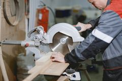 Cieśla w mundurze pracuje na cieśli ` s narzędziu dla ciąć drewno Obraz Stock