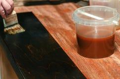 Cieśla zakrywa drewniane meblarskie części z drewnianym woskiem obrazy stock