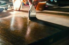 Cieśla zakrywa drewniane meblarskie części z drewnianym woskiem obraz stock