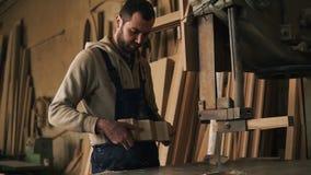 Cieśli sklep Ładny pracownik ciie żebrującego kształt od drewnianego bloku używać elektryczną saw maszynę Ocenia pracę zdjęcie wideo