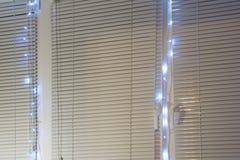 Ciechi chiusi della finestra decorati con splendere le ghirlande elettriche immagini stock libere da diritti