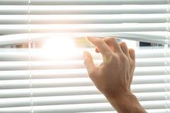 Ciechi di finestra di apertura del giovane, primo piano fotografie stock